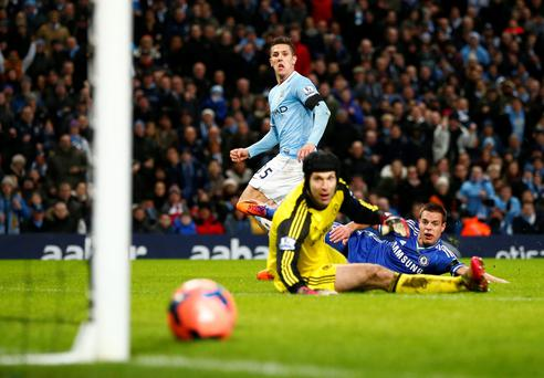 Manchester City's Stevan Jovetic (C) scores a goal as Chelsea's Petr Cech (L) and Cesar Azpilicueta react during their English FA Cup fifth round soccer match at the Etihad Stadium in Manchester.