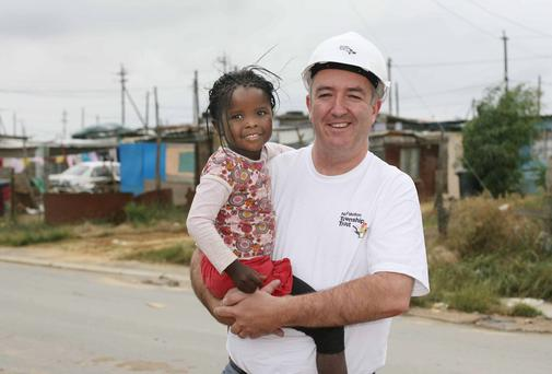 Niall Mellon meets a young resident of Wallacedene township, South Africa. Picture: Niall Carson/PA