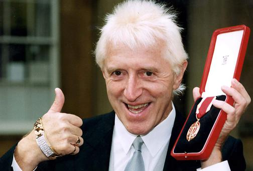 Jimmy Savile after he received his knighthood from Queen Elizabeth II in 1996. Picture: Jim James/PA Wire