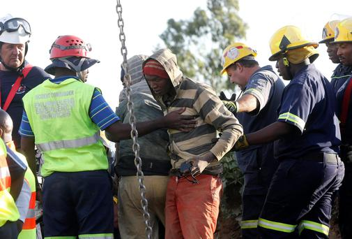 A suspected illegal miner is led away after being rescued from an abandoned gold shaft in Benoni, east of Johannesburg