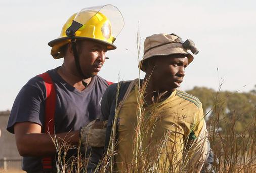 A suspected illegal miner is led away after being rescued from an abandoned gold shaft in Benoni, east of Johannesburg. South African rescuers started bringing to the surface at least 30 illegal miners on Sunday who had been trapped by debris in the abandoned gold shaft near Johannesburg, emergency services ER24 spokesman Werner Vermaak said. There were no immediate reports of deaths or injuries. Some of the miners still underground were refusing to come up, saying they did not want to be arrested. Photo: Reuters/Mike Hutchings