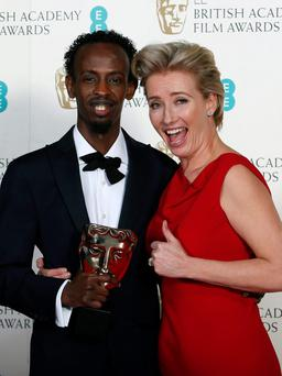 "Barkhad Abdi (L) celebrates winning Best Supporting Actor for ""Captain Phillips"" with Emma Thompson at the British Academy of Film and Arts (BAFTA) awards ceremony at the Royal Opera House in London February 16, 2014."