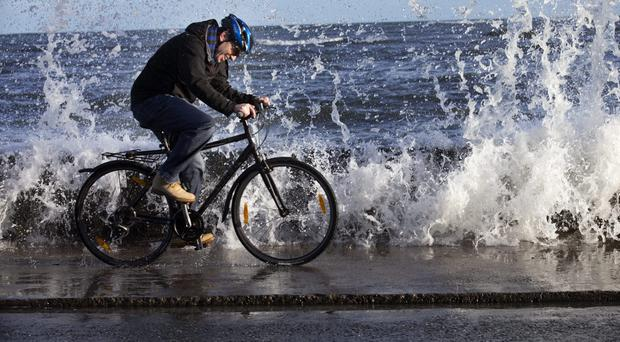 A cyclist braves the weather conditions on the coast road at Sandymount Photo: Tony Gavin