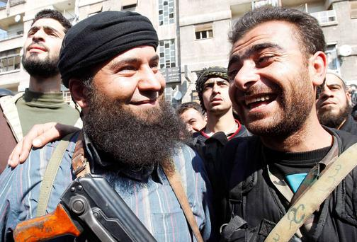A Syrian soldier, right, and a member of a rebel force share a joke in Damascus after a local ceasefire pact was reached