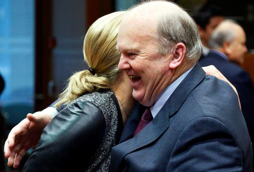 Finance Minister Michael Noonan greets his Finnish counterpart Jutta Urpilainen (L) during a European Union finance ministers meeting in Brussels yesterday.