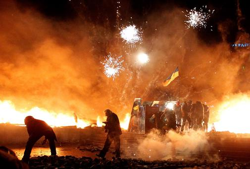 Fireworks explode amid flames during clashes between anti-government protesters and riot police at Kiev's Independence Square. Reuters