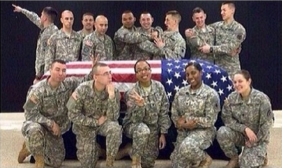 The Wisconsin Army National Guard soldier who posted this photo on social media of soldiers smiling or striking poses around a flag-draped casket has been suspended.