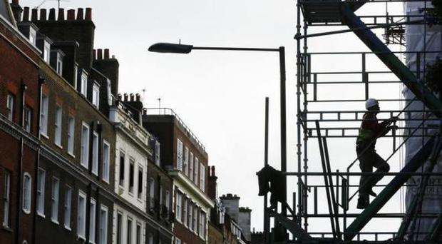 A scaffolder works on a site in London January 22, 2014. REUTERS/Luke MacGregor