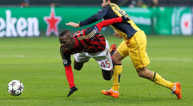 AC Milan's Mario Balotelli (L) is tackled by Atletico Madrid's Diego Costa during their Champions League round of 16 first leg soccer match at the San Siro stadium in Milan February 19, 2014. REUTERS/Alessandro Bianchi