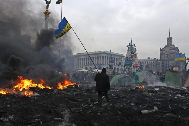 An anti-government protester carry the national flag as he walks trough the rubble after violence erupted in the Independence Square in Kiev