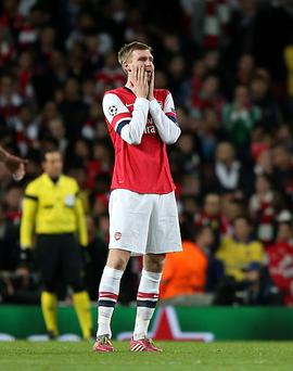 Arsenal's Per Mertesacker stands dejected after they concede the opening goal of the game during the UEFA Champions League, Round of 16 match at the Emirates Stadium, London. PRESS ASSOCIATION Photo.