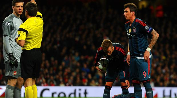 Referee Nicola Rizzoli shows Wojciech Szczesny of Arsenal a red card for a foul on Arjen Robben of Bayern Muenchen.