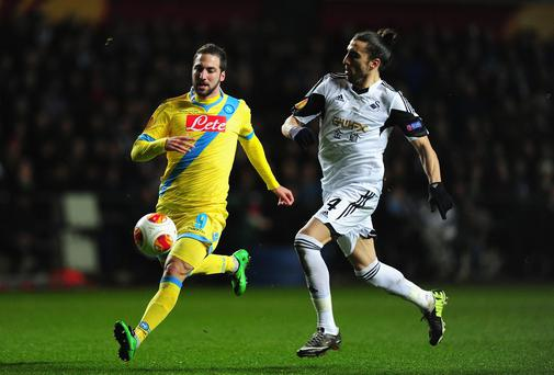 Swansea player Chico Flores (r) challenges the Napoli striker Gonzalo Higuain during the UEFA Europa League Round of 32 first leg between Swansea City and SSC Napoli at Liberty Stadium
