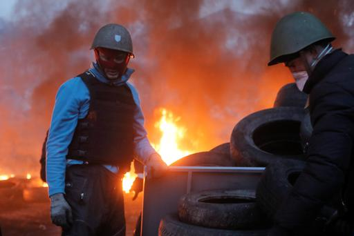 Activist carries a tyre at the burning barricades, close to Independence Square, the epicenter of the country's current unrest, in Kiev, Ukraine. Photo: AP Photo/Efrem Lukatsky