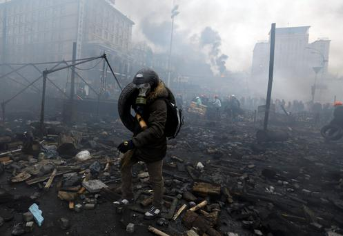 An anti-government protester carries a tyre through the rubble after violence erupted in the Independence Square in Kiev February 20, 2014. Photo: REUTERS/Yannis Behrakis