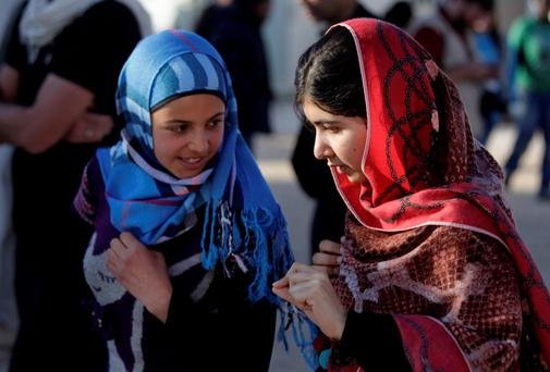 Taliban victim Malala Yousafzai (right) with a Syrian refugee. PA