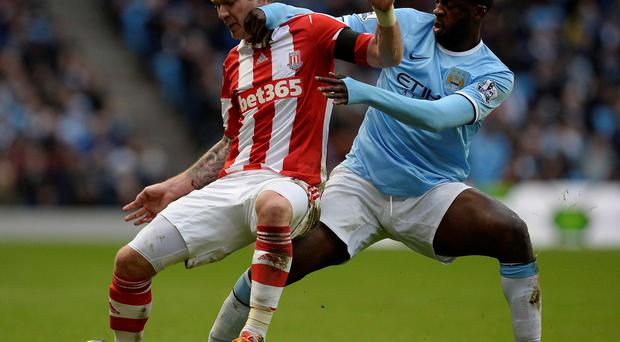 Manchester City's Yaya Toure (R) challenges Stoke City's Glenn Whelan during their English Premier League soccer match at the Etihad Stadium in Manchester, northern England