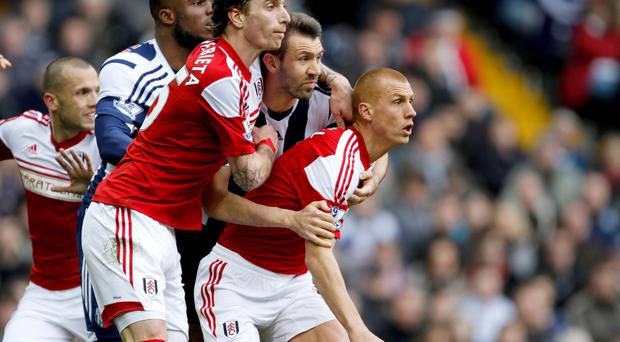 Fulham's Fernando Amorebieta, centre and Steve Sidwell (right) control West Brom's Gareth McAuley during the Barclays Premier League match at The Hawthorns, West Bromwich