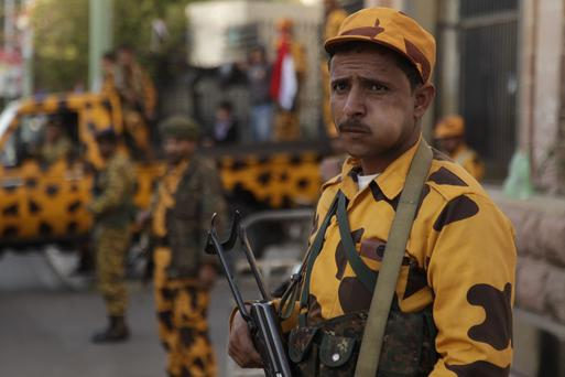 Police troopers stand guard as pro-democracy protesters march on a street in Sanaa