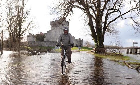 A man cycling through flooded road in Killarney last week