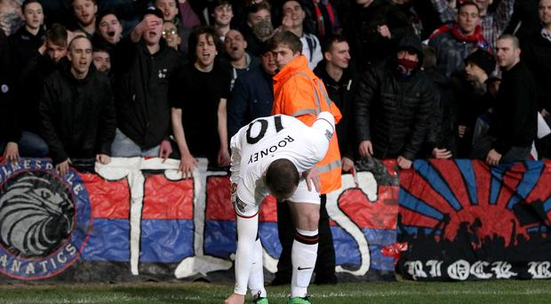 Manchester United's Wayne Rooney picks up an object that was thrown from the crowd during the Barclays Premier League match at Selhurst Park