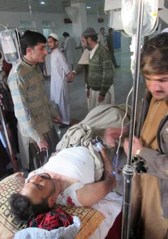 A Pakistani man, who was injured in a bomb blast in Kohat, receives treatment at a hospital in Peshawar, Pakistan, Sunday, Feb. 23, 2014. A bomb planted at a busy bus terminal near a police station in northwest Pakistan exploded Sunday, killing several people and wounding many near the country's lawless tribal region, authorities said. The explosion targeted passengers in a motorized rickshaw and those on a mini-bus in Kohat, some 150 kilometers (100 miles) west of the capital, Islamabad, police official Iqbal Khan said. (AP Photo/Mohammed Zubair)