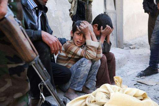 Children weep next to the body of their mother who activists say was killed by Assad loyalists.
