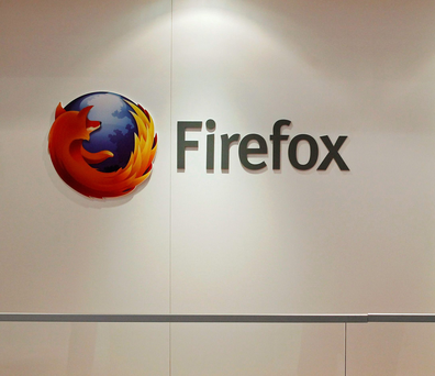A man is seen next to a Firefox logo at a Mozilla stand during the Mobile World Congress in Barcelona, in this February 28, 2013 file picture. A paper released by the mobile industry's GSM Association ahead of this week's congress in Barcelona noted that at least 36 telecoms operators had pledged support for one of the four open source challengers - Firefox, Ubuntu, Tizen and Sailfish
