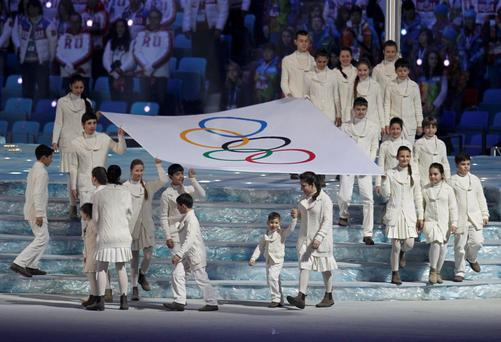 Children carry the Olympic flag during the closing ceremony for the 2014 Sochi Winter Olympics