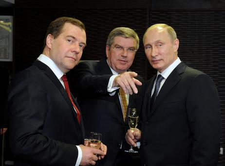 Russia's President Vladimir Putin (R), Prime Minister Dmitry Medvedev (L) and International Olympic Committee (IOC) President Thomas Bach of Germany speak before the closing ceremony for the 2014 Sochi Winter Olympics February 23, 2014