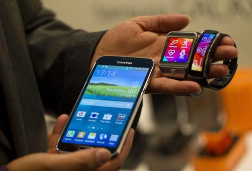 The Samsung Galaxy S5 smartphone, Gear 2 smartwatch and Gear Fit fitness band are displayed at the Mobile World Congress in Barcelona.