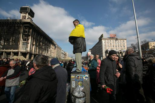 A man attends a prayer at Kiev's Independence Square