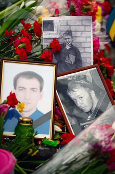 Pictures are left with flowers in Independence Square, where dozens of protestors were killed in clashes with riot police last week on February 25, 2014 in Kiev, Ukraine