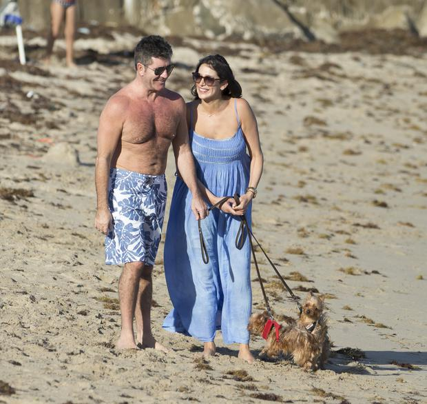 Simon Cowell and Lauren Silverman enjoy the beach with their dogs in FL. The two were spotted taking a walk with their two dogs and lounged by the sea for a little bit at the end of a gorgeous day in Miami.