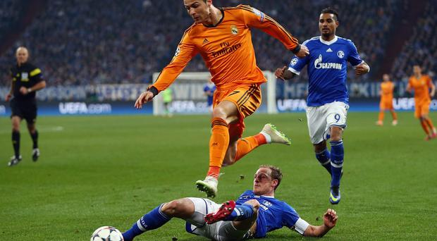 Cristiano Ronaldo of Madrid eludes Benedikt Hoewedes and Kevin-Prince Boateng (back) of Schalke