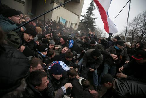 Ukrainian men help pull one another out of a stampede as a flag of Crimea is seen during clashes at rallies held by ethnic Russians and Crimean Tatars near the Crimean parliament building in Simferopol