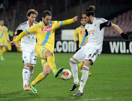 Napoli's Gonzalo Higuain, left, and Swansea's Chico vie for the ball during an Europe League, round of 32, second leg, soccer match between Napoli and Swansea