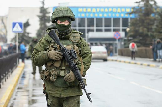Soldiers, who were wearing no identifying insignia and declined to say whether they were Russian or Ukrainian, patrol outside the Simferopol International Airport after a pro-Russian crowd had gathered on February 28, 2014 near Simferopol, Ukraine