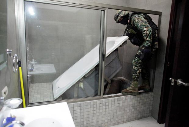 A Mexican marine lifts a bathtub that leads to a tunnel and exits in the city's drainage system at one of the houses of Joaquin 'Chapo' Guzman in Culiacan. Guzman, who rose from humble origins to become one of the most powerful drug barons in history, was captured on Saturday in a raid in the beachside resort and fishing center of Mazatlan, 125 miles southeast of Culiacan, just days after escaping from the clutches of Mexican troops through the tunnel and sewers. Reuters