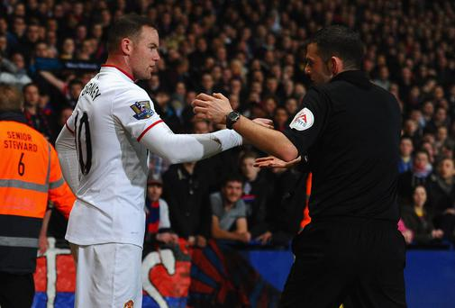 Wayne Rooney hands over a coin thrown from the crowd to referee Michael Oliver at Selhurst Park last week