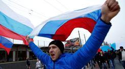 People march on the streets with Russian flags in Simferopol, Crimea March 1, 2014. Russian President Vladimir Putin has asked the upper house of parliament to approve sending armed forces to Ukraine's Crimea region, the Kremlin said in a statement on Saturday. REUTERS/David Mdzinarishvili