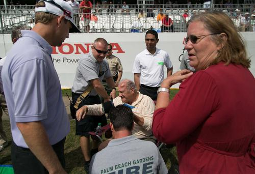 Spectator Edwin Curtis, of Palm Beach Gardens, center, receives attention after being hit by a ball near the 18th green during the second round of the Honda Classic in Palm Beach Gardens.