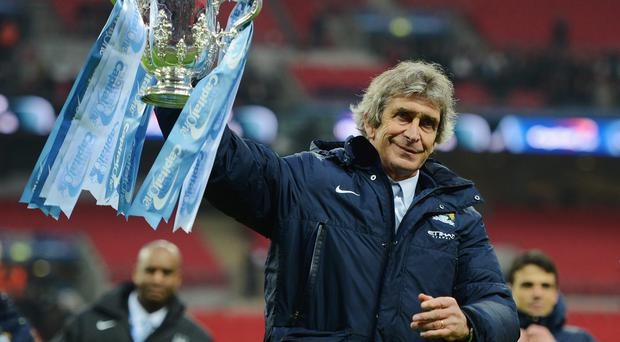 Manuel Pellegrini celebrates victory with the trophy after the Capital One Cup Final between Manchester City and Sunderland at Wembley.
