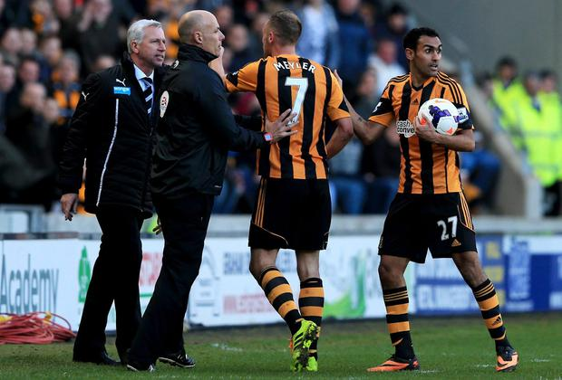 Fourth official Howard Webb restrains David Meyler of Hull City after a clash with Alan Pardew manager of Newcastle United