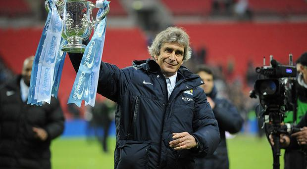 Manchester City manager Manuel Pellegrini celebrates with the Capital One Cup after the Capital One Cup Final at Wembley
