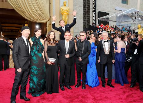 Best Oscars photo-bomb? Actor Benedict Cumberbatch jumps behind U2 at the 86th Academy Awards in Hollywood, California March 2, 2014. REUTERS/Mike Blake