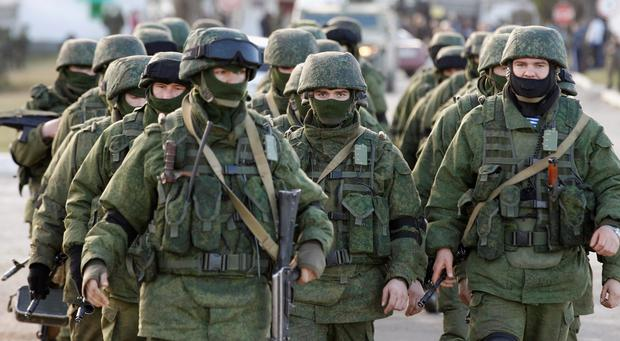 Military personnel, believed to be Russian servicemen, walk outside the territory of a Ukrainian military unit in the village of Perevalnoye outside Simferopol today. Photo: Reuters