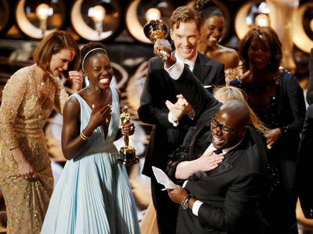 Director and producer Steve McQueen celebrates after accepting the Oscar for Best Picture with Lupita Nyong'o (L) at the 86th Academy Awards in Hollywood, California March 2, 2014. REUTERS/Lucy Nicholson