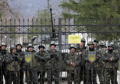 Ukrainian soldiers guard a gate of an infantry base in Privolnoye, Ukraine