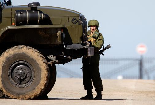 A military personnel member, believed to be a Russian serviceman, stands guard near a local airfield, near the territory of a Ukrainian military unit in the village of Lyubimovka, some 80 km (50 miles) southwest of Simferopol, Crimea's capital